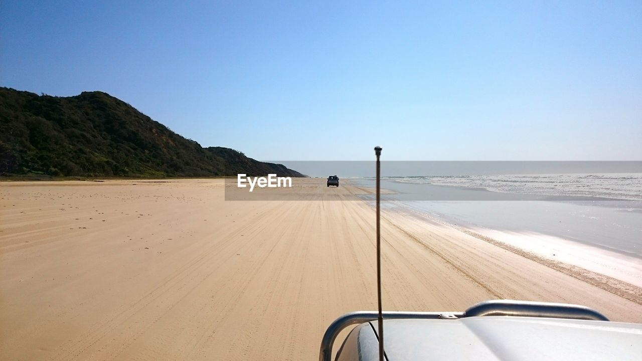 Off-Road Vehicle On Shore At Beach Against Sky