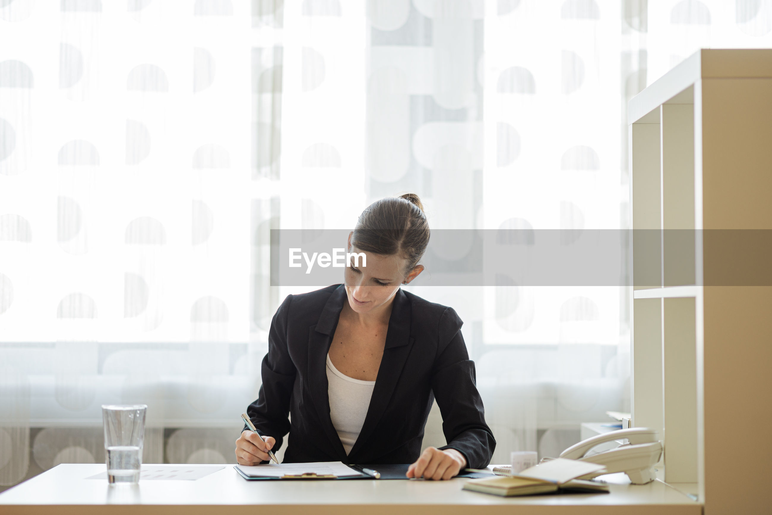 YOUNG WOMAN WORKING ON TABLE IN OFFICE