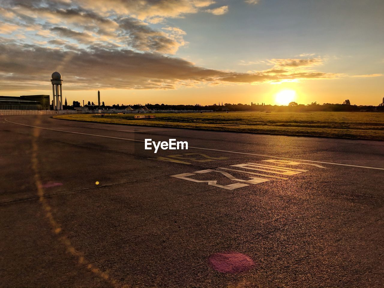 View of airport runway against sky during sunset