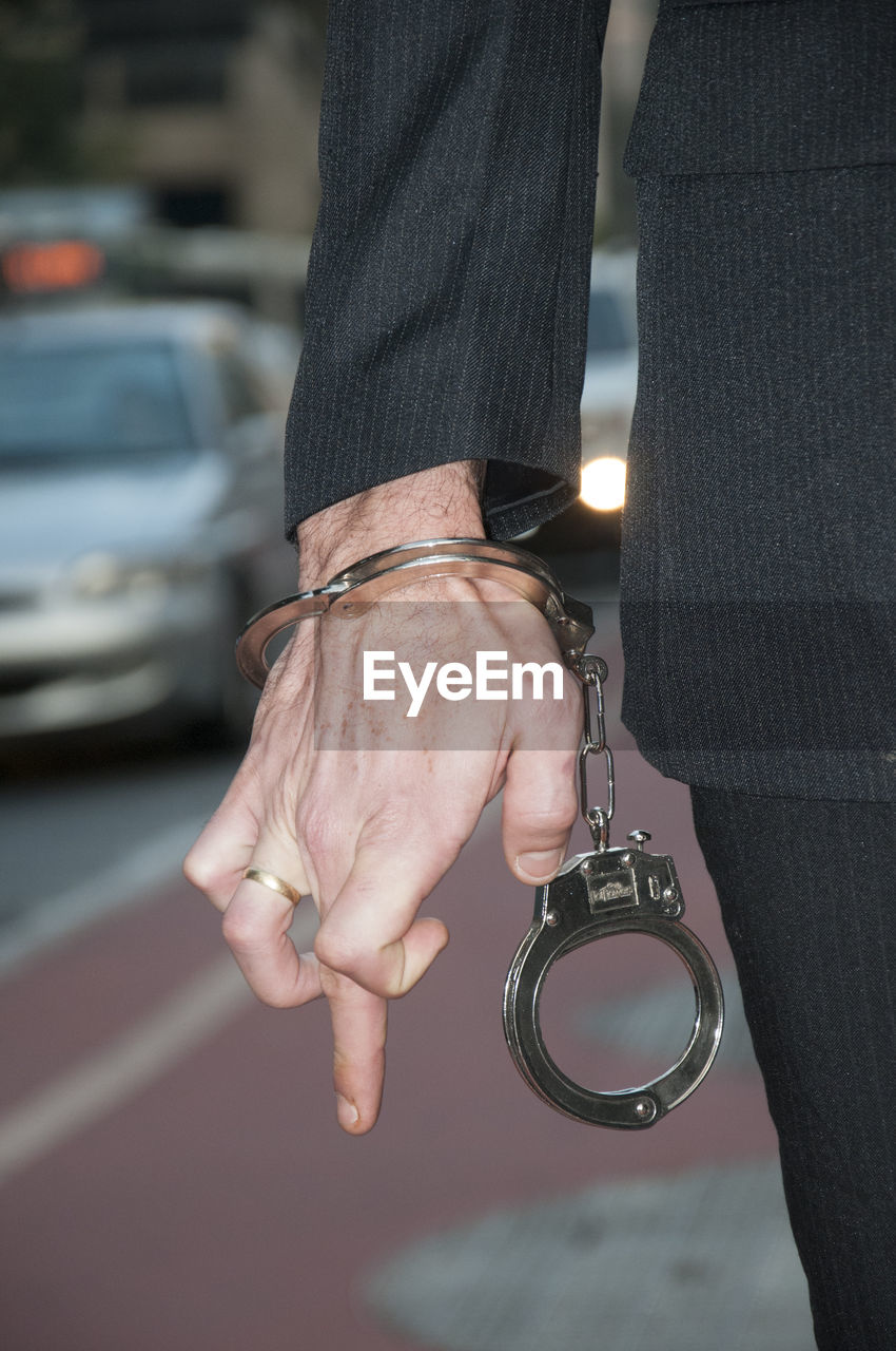 Midsection Of Man With Handcuffs Standing On Street