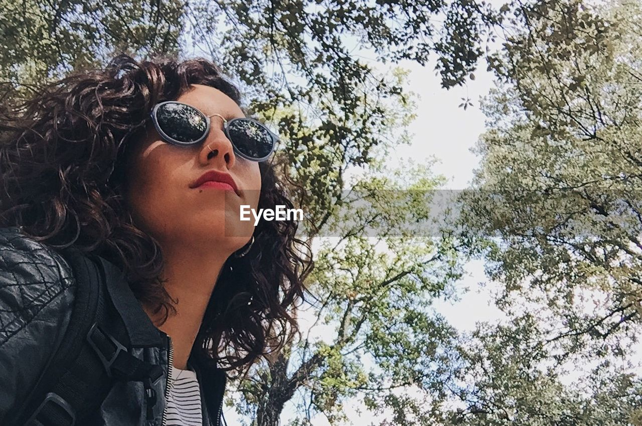 tree, sunglasses, real people, young women, lifestyles, one person, day, young adult, low angle view, outdoors, nature, beautiful woman, people