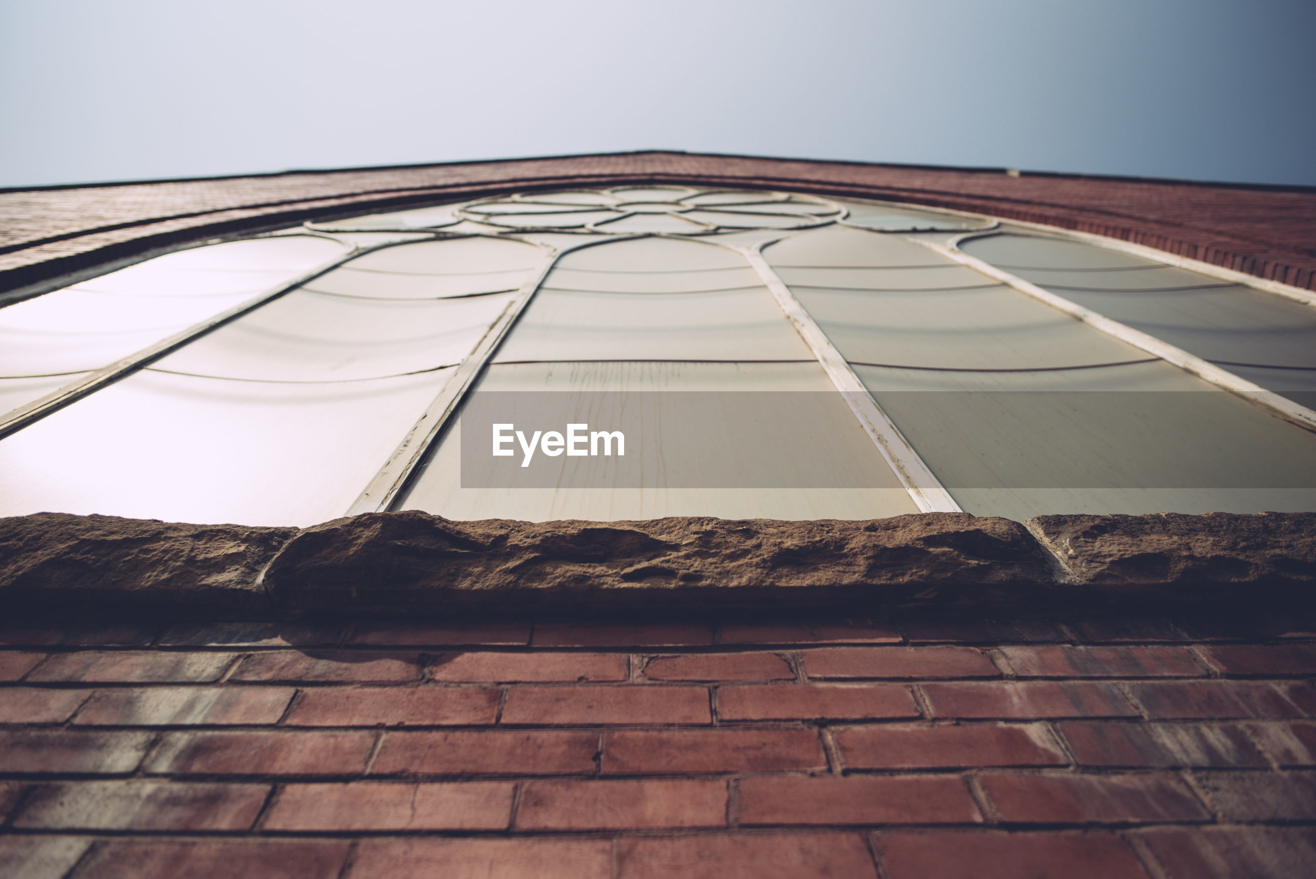 Low angle view of building window against clear sky