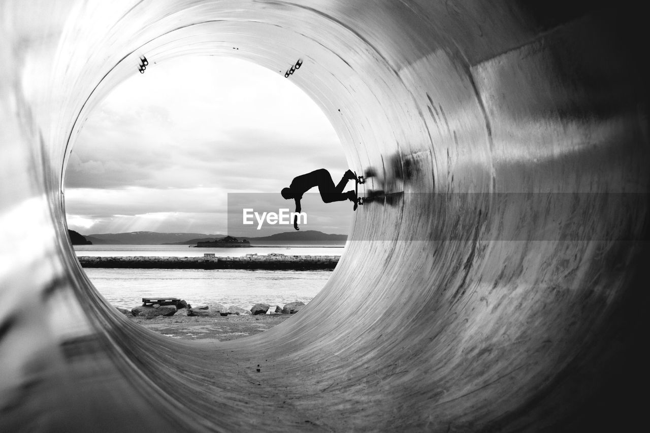 Silhouette Man Skateboarding In Cement Pipe At Beach