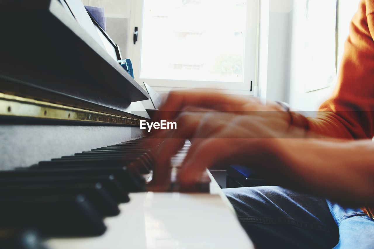 Cropped Image Of Hand Playing Piano At Home