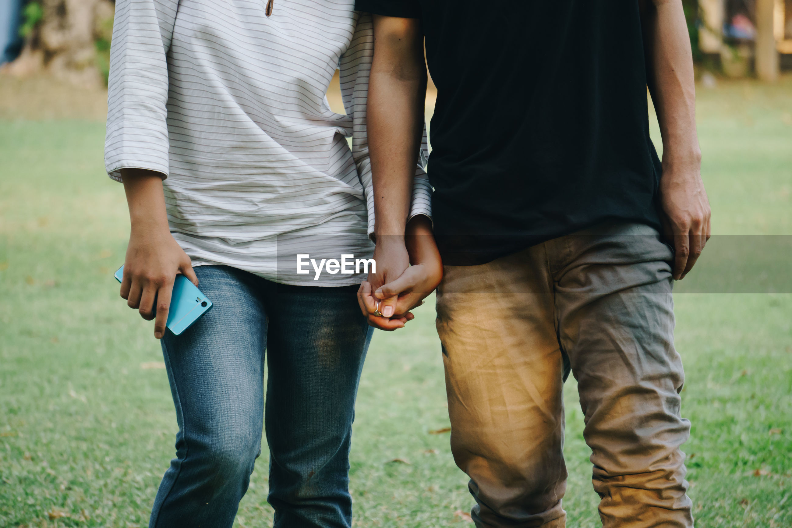 Midsection of couple holding hands while standing in park