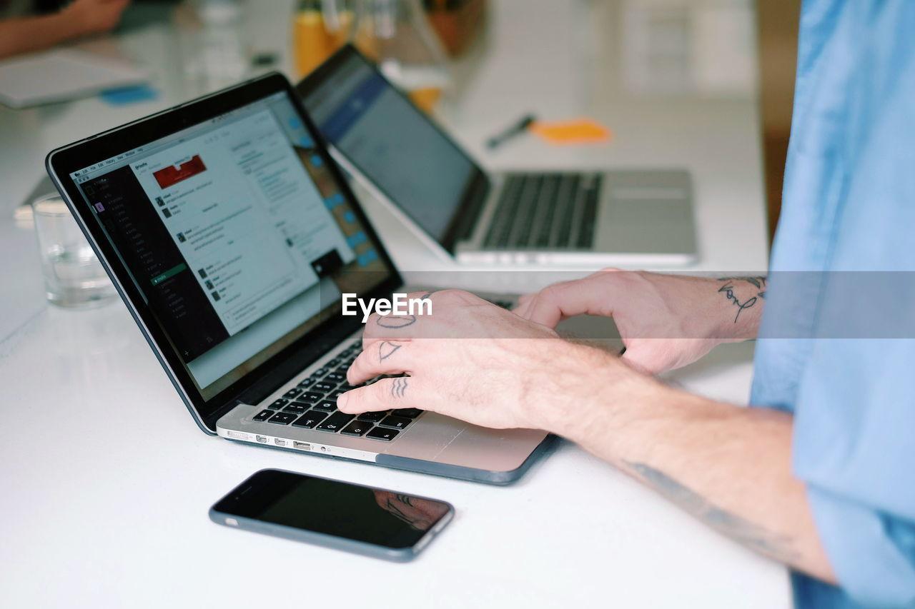 Cropped image of man using laptop