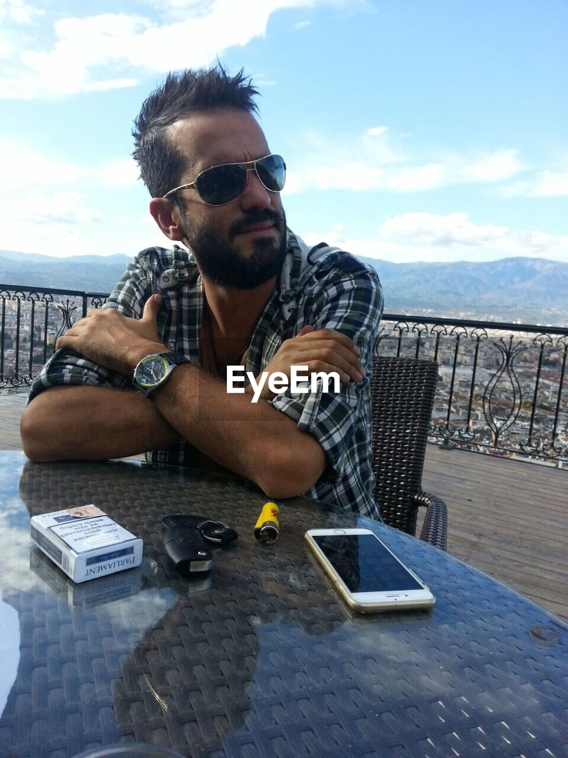 lifestyles, young men, sunglasses, leisure activity, young adult, sky, person, looking at camera, casual clothing, portrait, photography themes, holding, front view, sitting, mid adult, mid adult men, technology, photographing