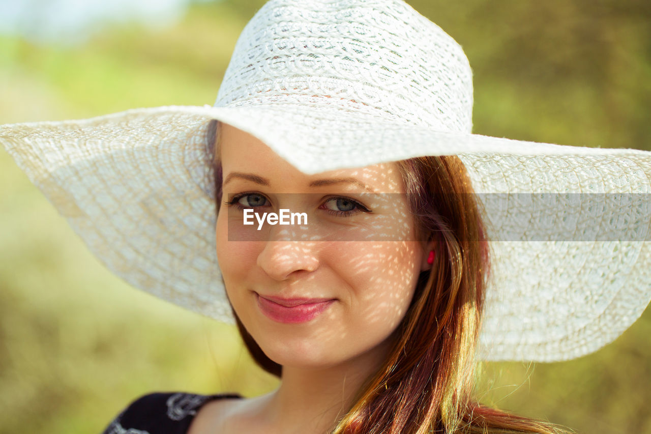 hat, portrait, headshot, focus on foreground, looking at camera, real people, one person, leisure activity, young women, clothing, women, smiling, lifestyles, close-up, young adult, front view, sun hat, day, adult, emotion, beautiful woman, hairstyle, human face