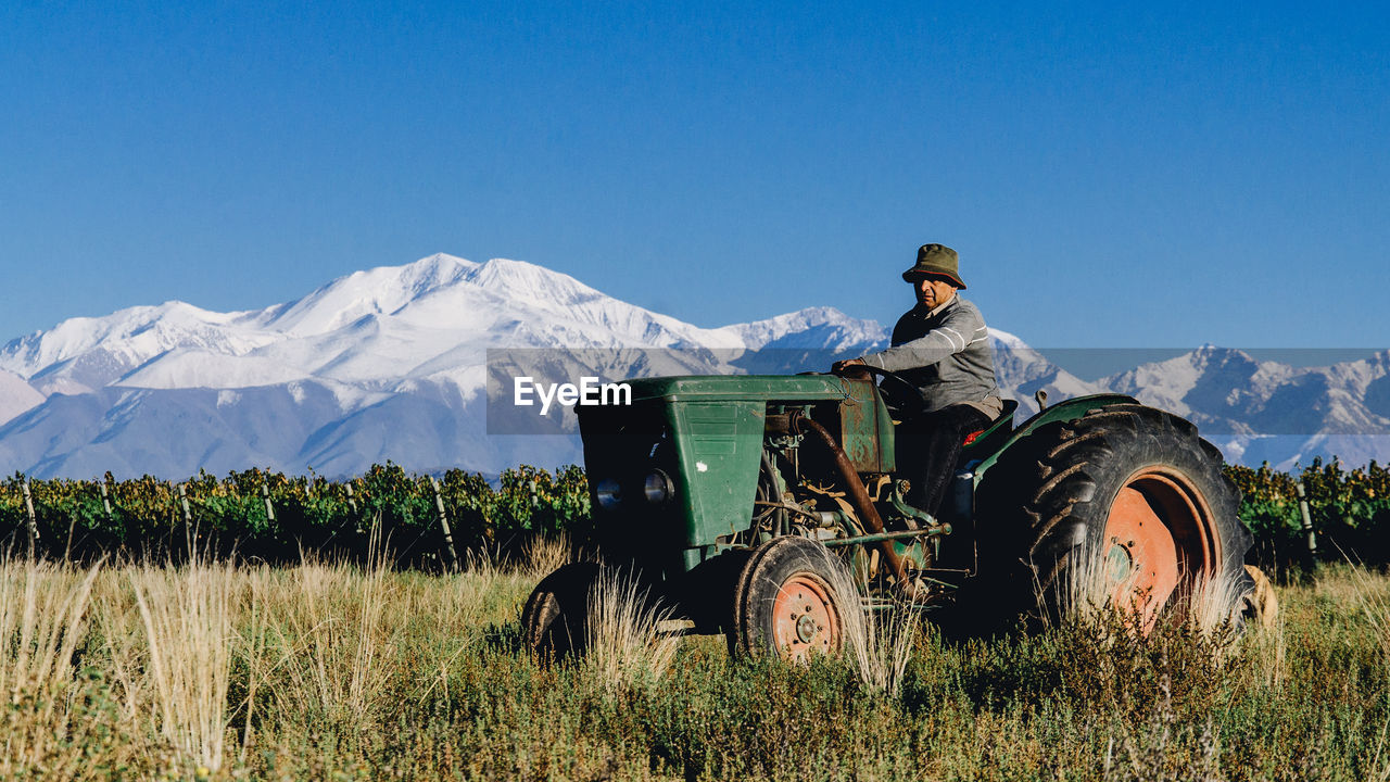 Man Driving Tractor On Grassy Field By Vineyard Against Snowcapped Mountains