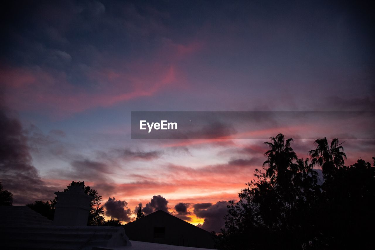 sky, cloud - sky, sunset, silhouette, beauty in nature, scenics - nature, orange color, tree, nature, plant, no people, architecture, low angle view, tranquility, house, idyllic, tranquil scene, built structure, dramatic sky, building exterior, romantic sky