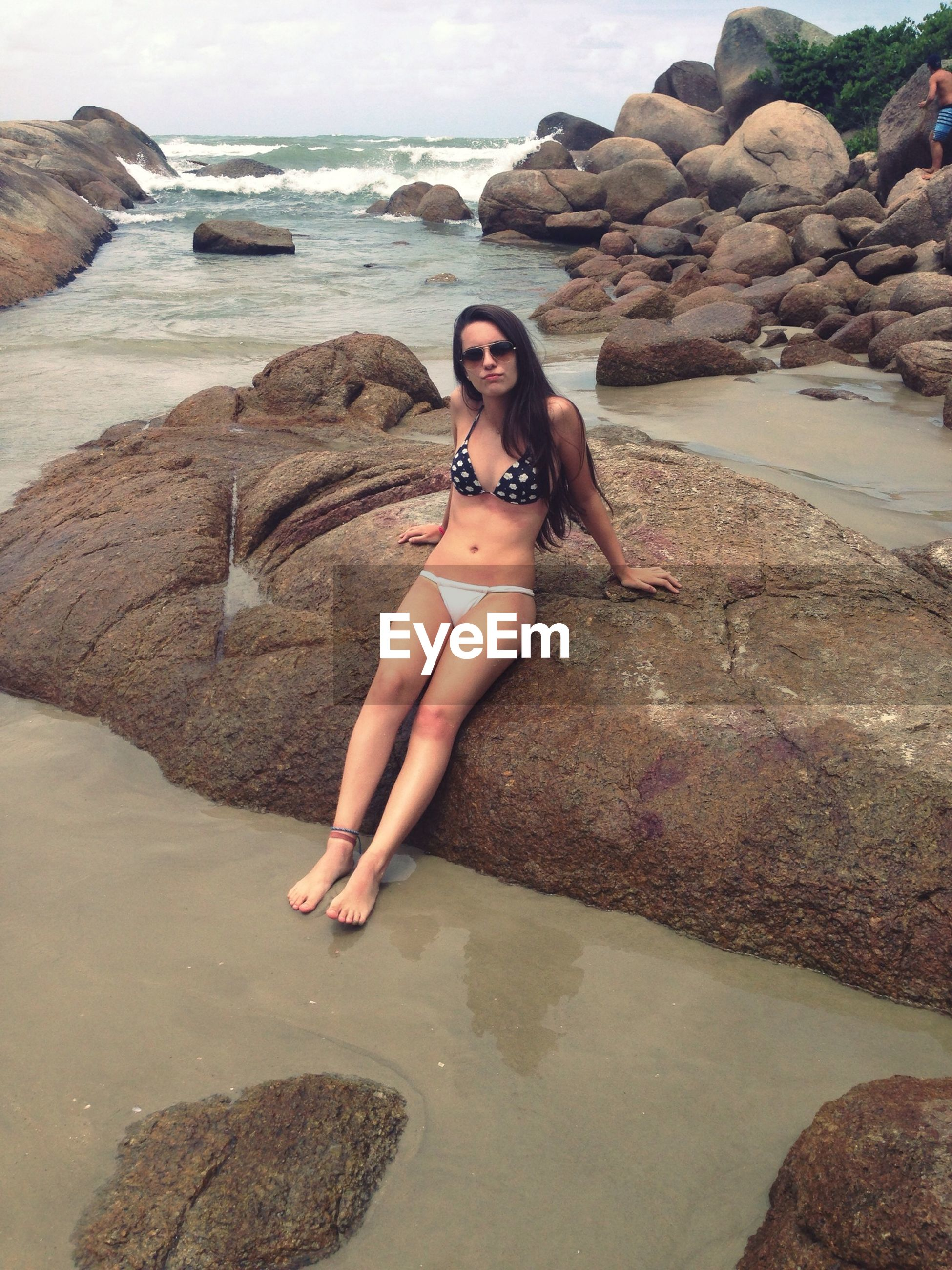 water, sea, lifestyles, beach, leisure activity, young adult, person, young women, rock - object, shore, vacations, looking at camera, portrait, full length, sitting, casual clothing, sunglasses