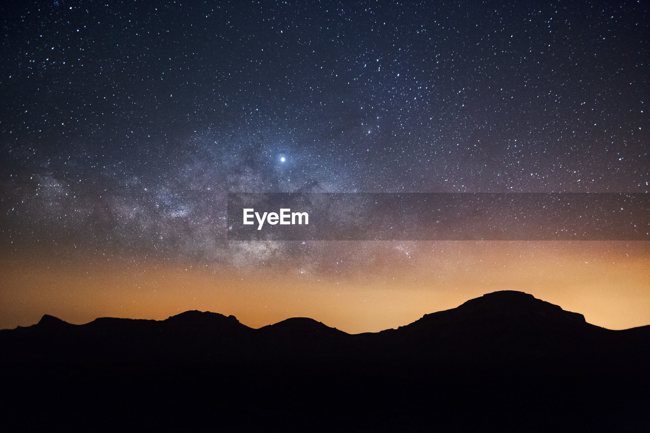 Scenic view of silhouette mountain against milky way sky at night