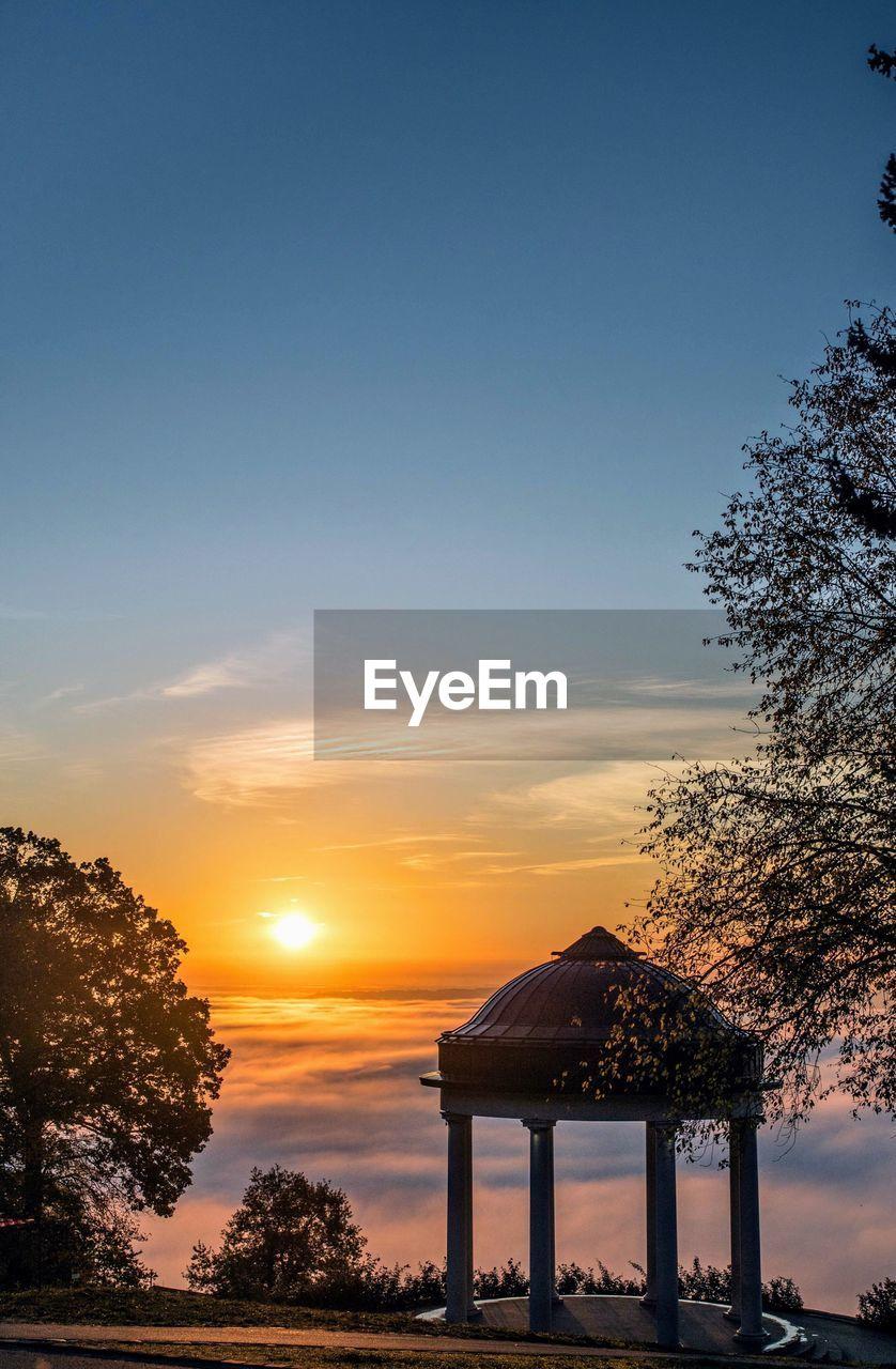 Gazebo on mountain against sky during sunset