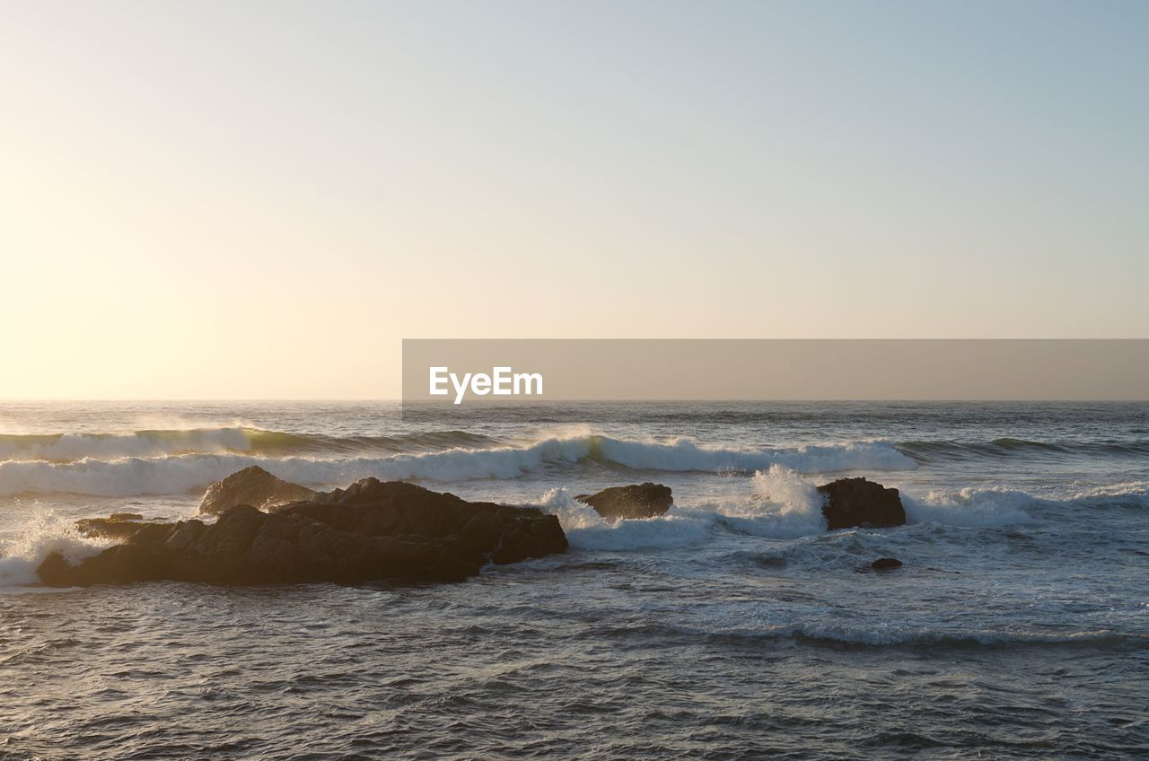 sea, sky, water, horizon, horizon over water, scenics - nature, beauty in nature, beach, motion, wave, land, clear sky, tranquility, nature, copy space, sunset, rock, no people, sport, outdoors, power in nature