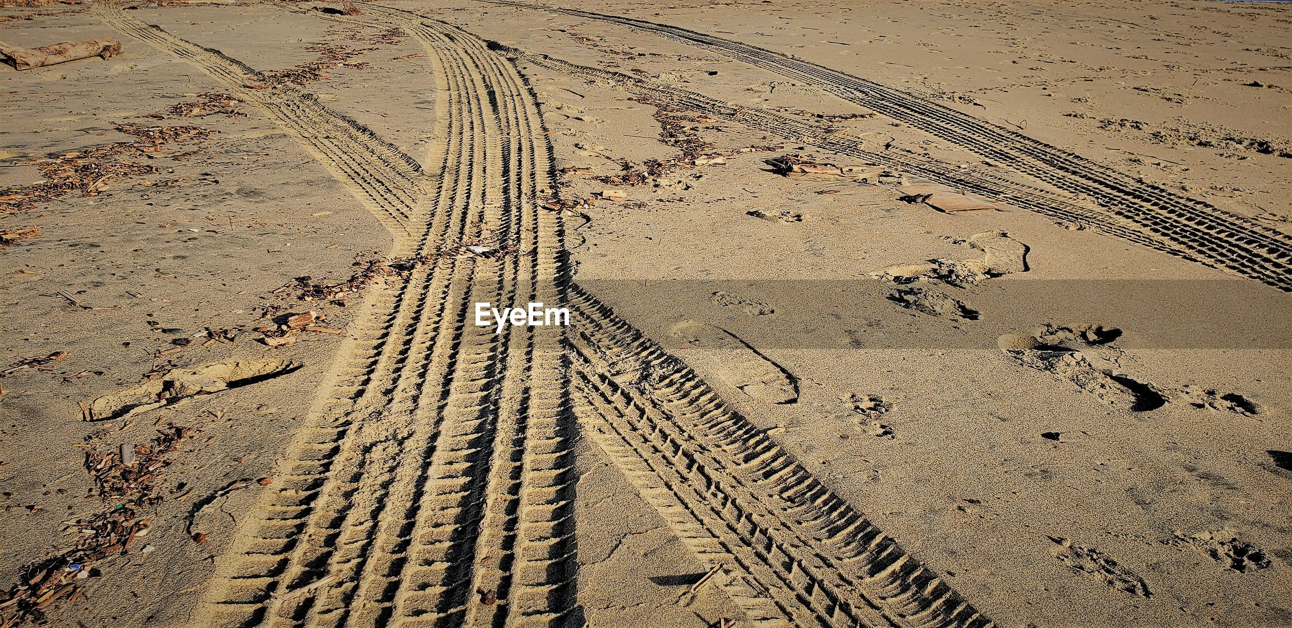 HIGH ANGLE VIEW OF TIRE TRACK ON SAND