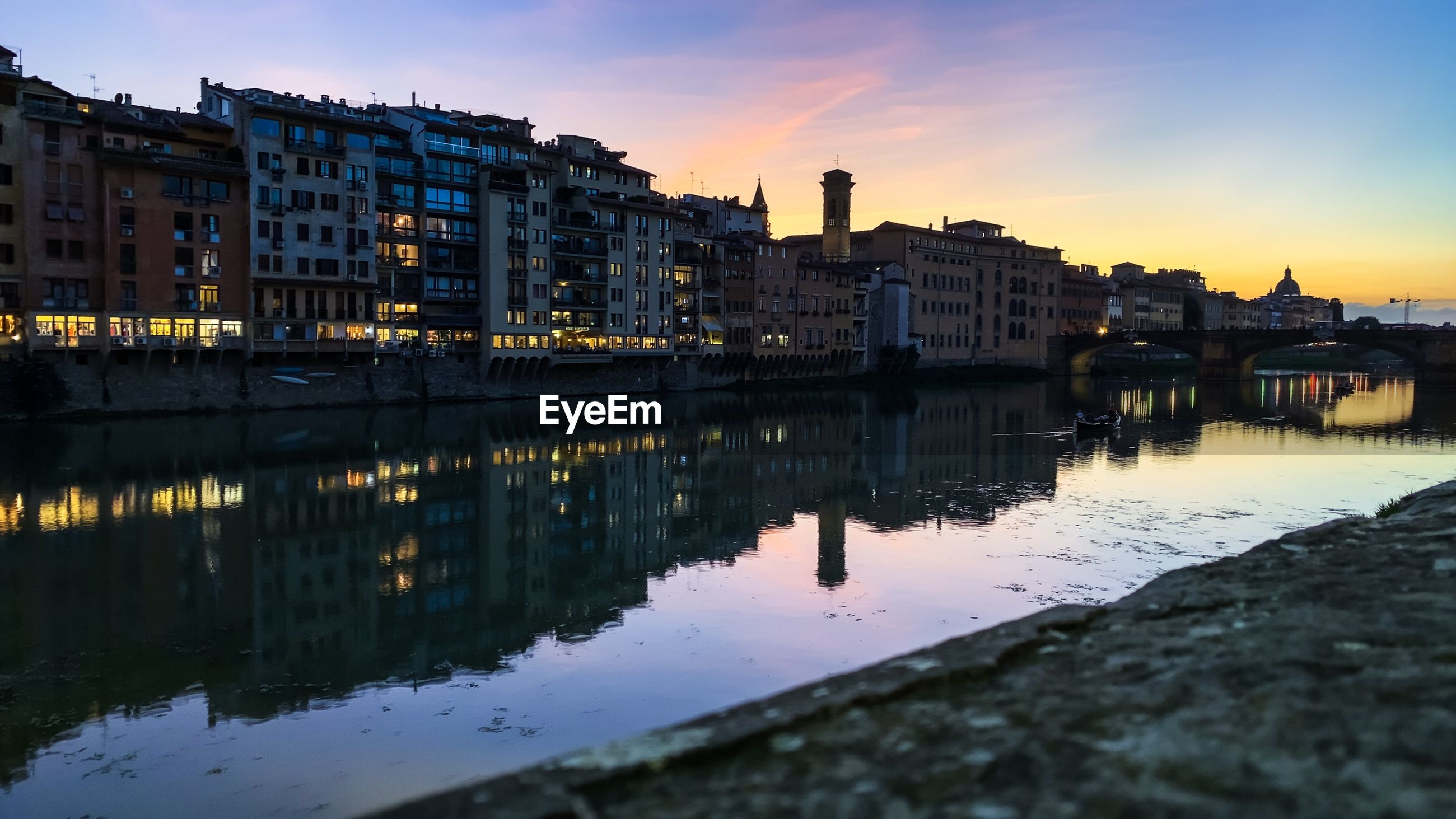 River by illuminated buildings against sky at sunset