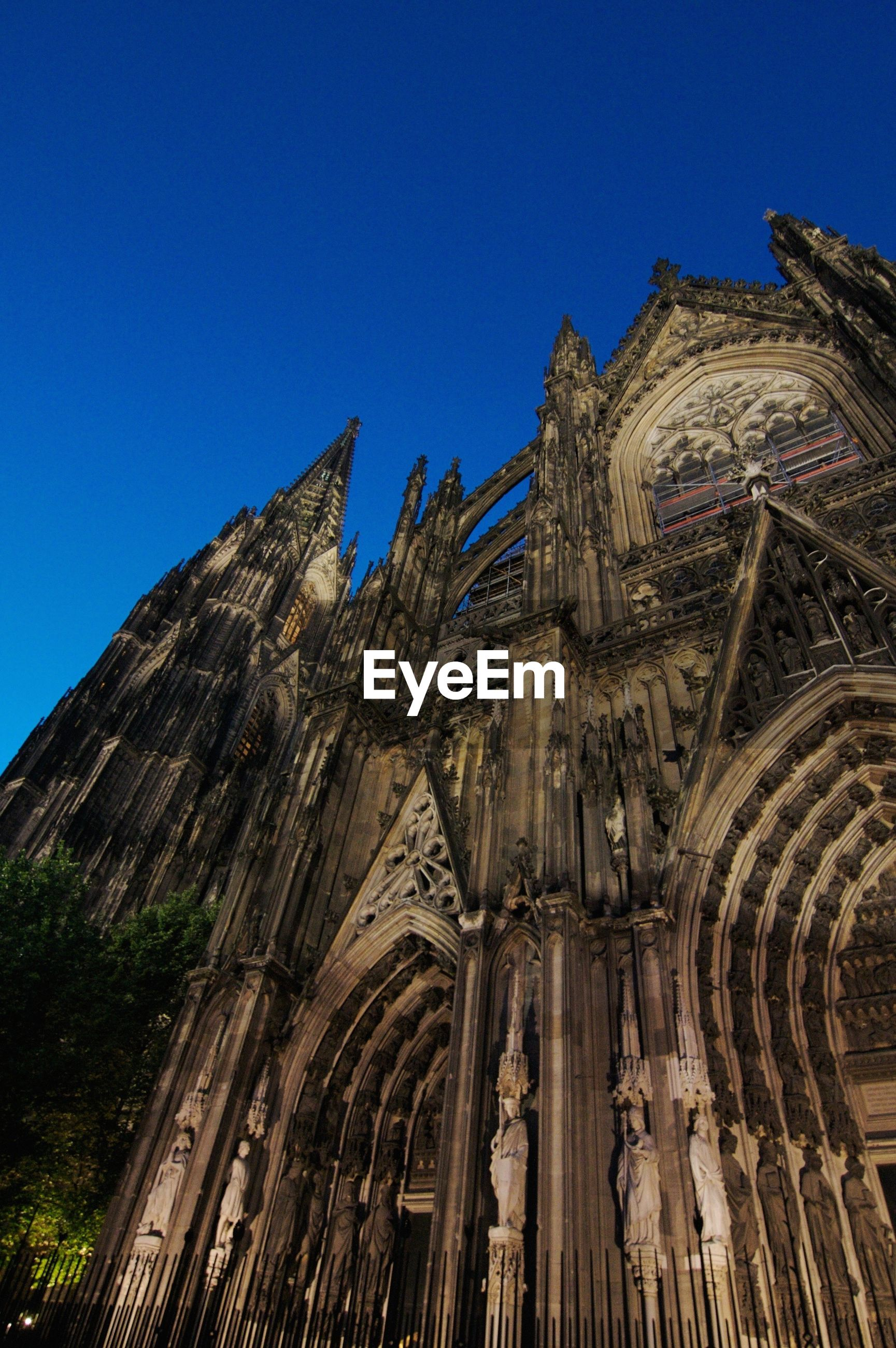 Low angle view of cologne cathedral against clear blue sky at dusk