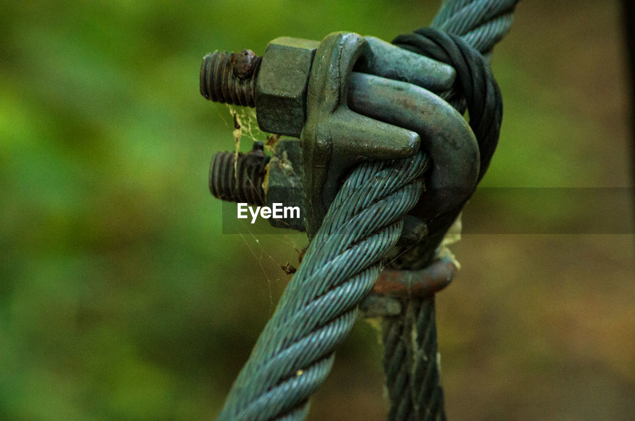rope, focus on foreground, close-up, connection, no people, day, strength, metal, tied up, outdoors, pattern, tied knot, nature, green color, durability, chain, selective focus, steel cable, rusty, still life
