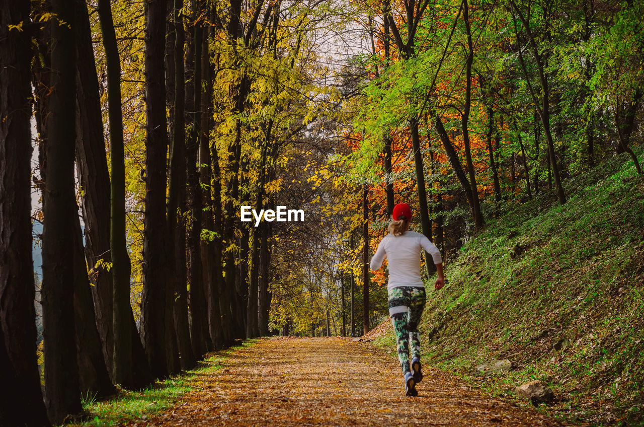 Rear View Of Woman Running On Pathway In Forest During Autumn