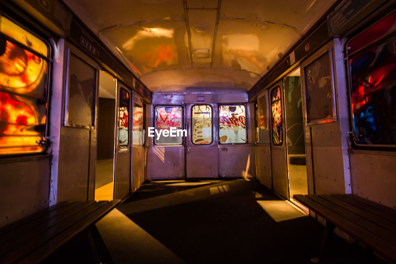 illuminated, indoors, public transportation, transportation, architecture, mode of transportation, no people, window, empty, vehicle interior, glass - material, train, absence, built structure, rail transportation, graffiti, transparent, vehicle seat, ceiling