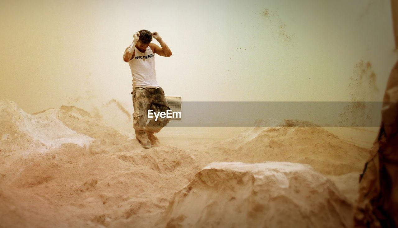 Full length of messy artist walking amidst powdered plaster at workshop