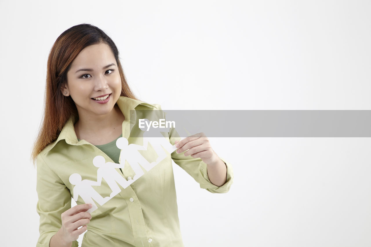 Portrait Of Confident Young Woman Holding People Paper Chain Against White Background