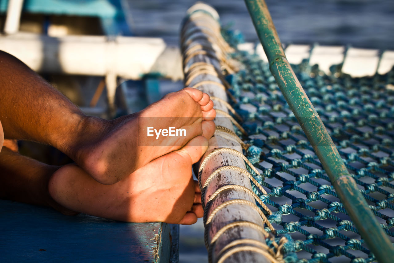 Low section of man relaxing by fishing net on boat