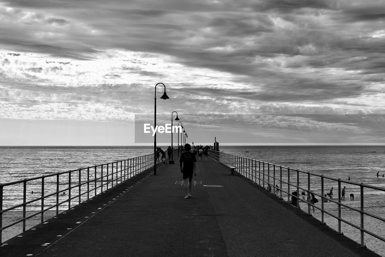 sea, horizon over water, water, cloud - sky, sky, railing, fishing pole, nature, real people, scenics, one person, tranquil scene, beach, beauty in nature, walking, men, outdoors, tranquility, full length, standing, day, one man only, people