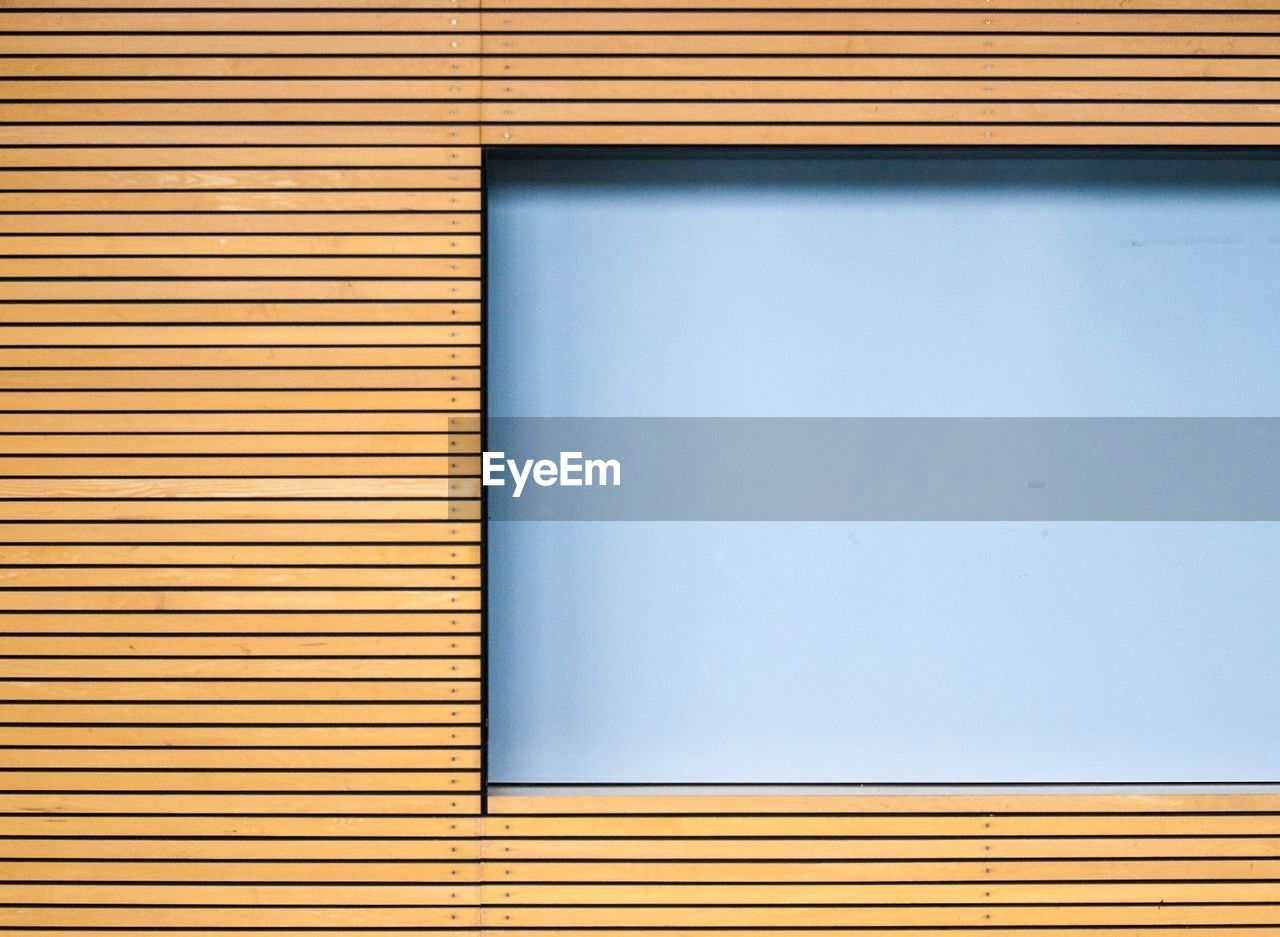 Glass window by wooden wall
