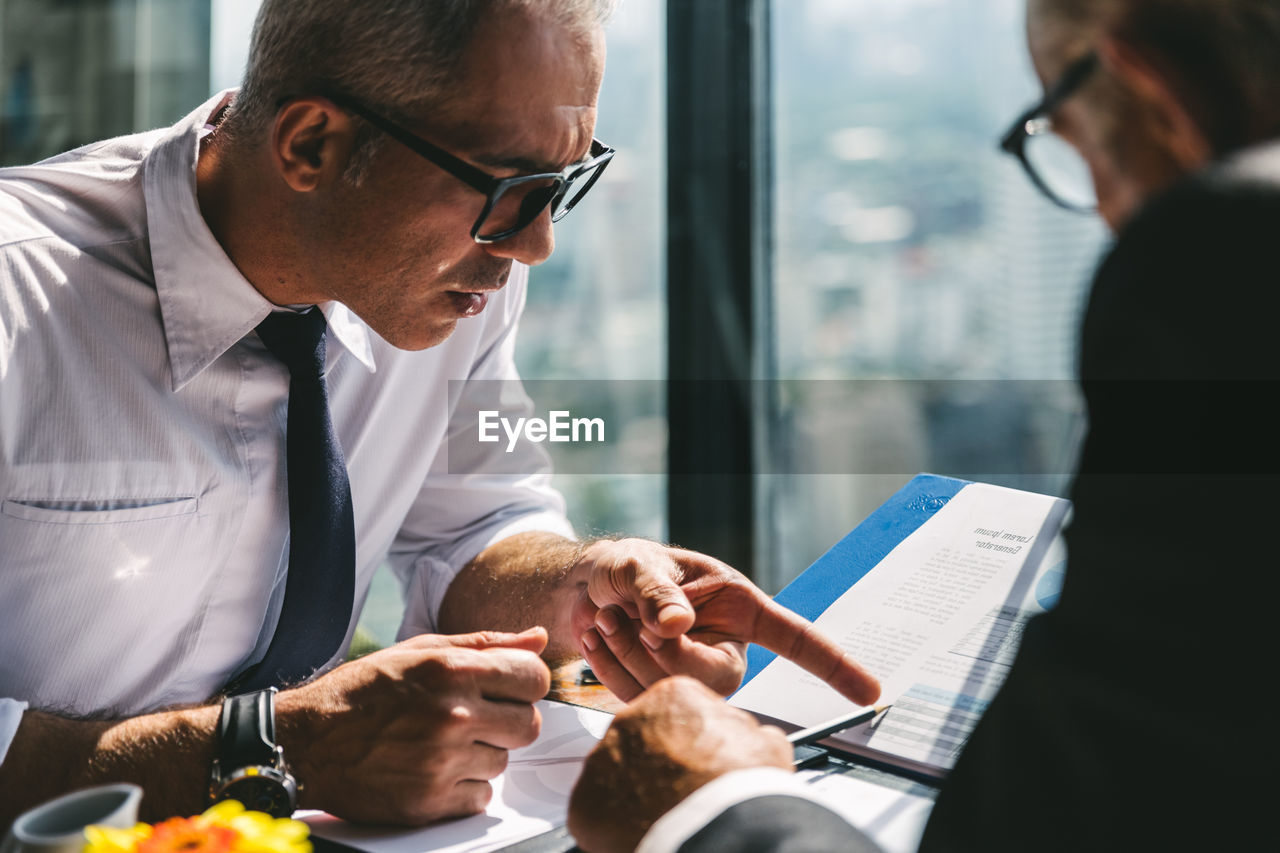 Man wearing eyeglasses having discussion with colleague in office