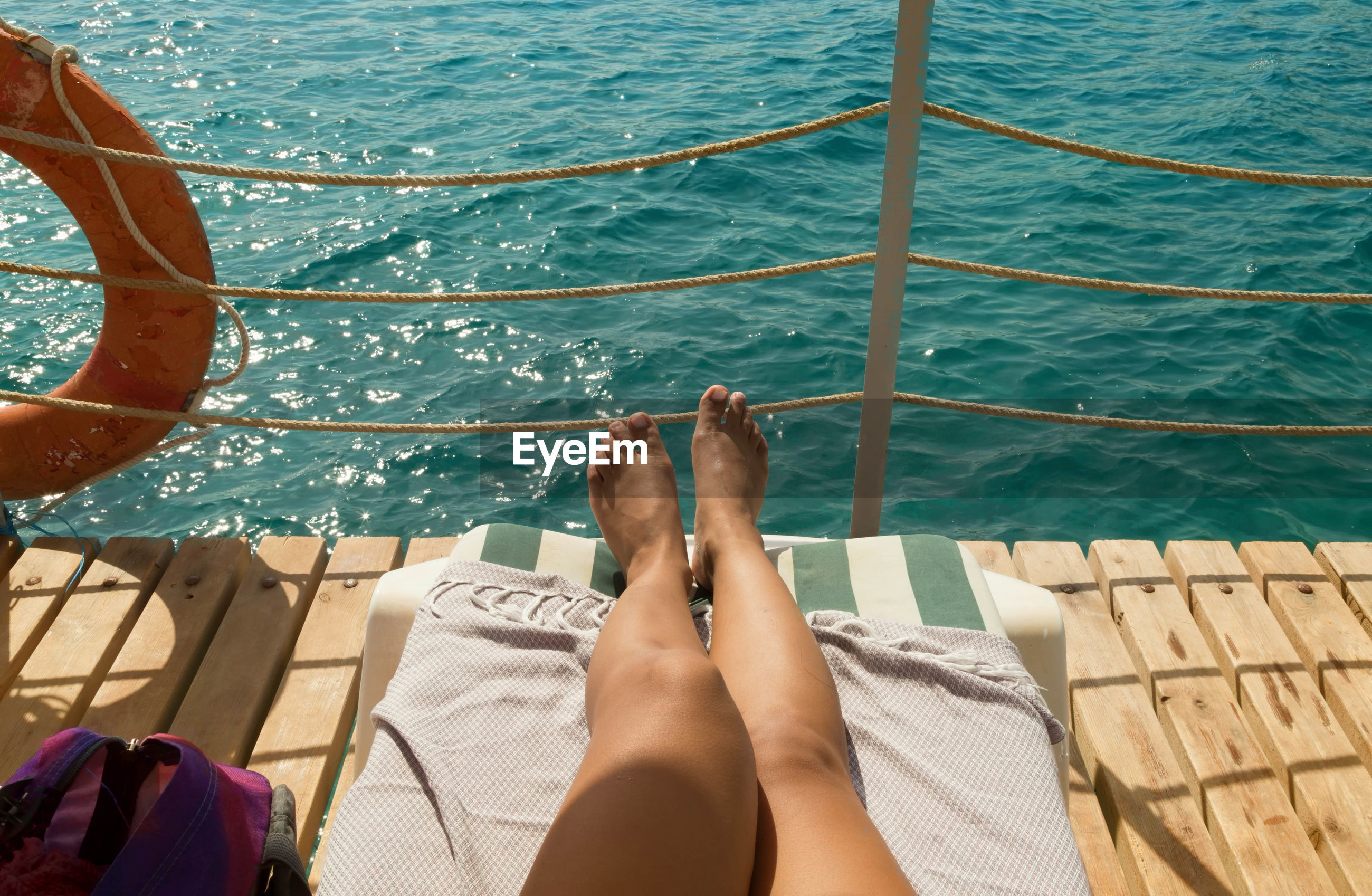 Low section of woman sunbathing on pier over sea