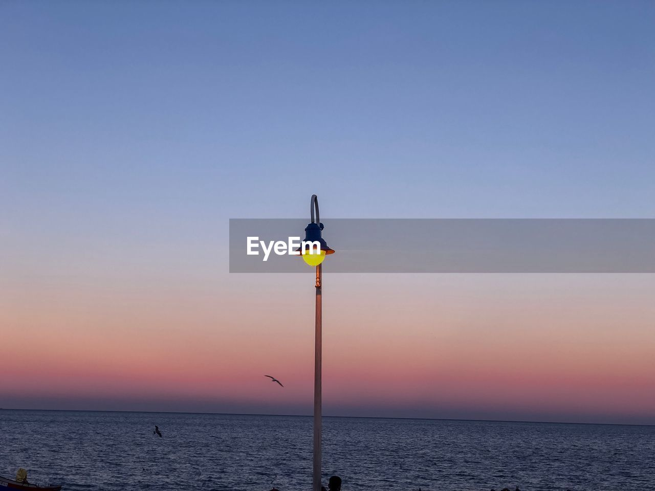 sky, water, sunset, sea, beauty in nature, lighting equipment, horizon over water, scenics - nature, horizon, tranquility, street light, copy space, street, pole, tranquil scene, nature, clear sky, illuminated, no people, outdoors, electric lamp