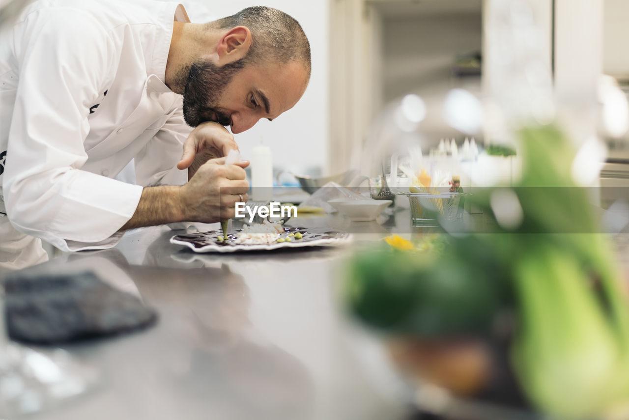Side view of chef garnishing food