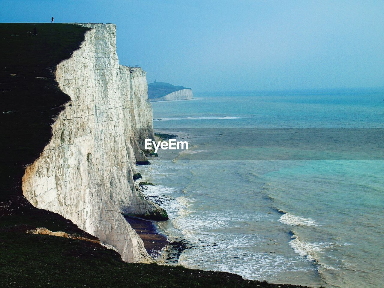 Idyllic view of sea against blue sky with cliff in seven sisters country park