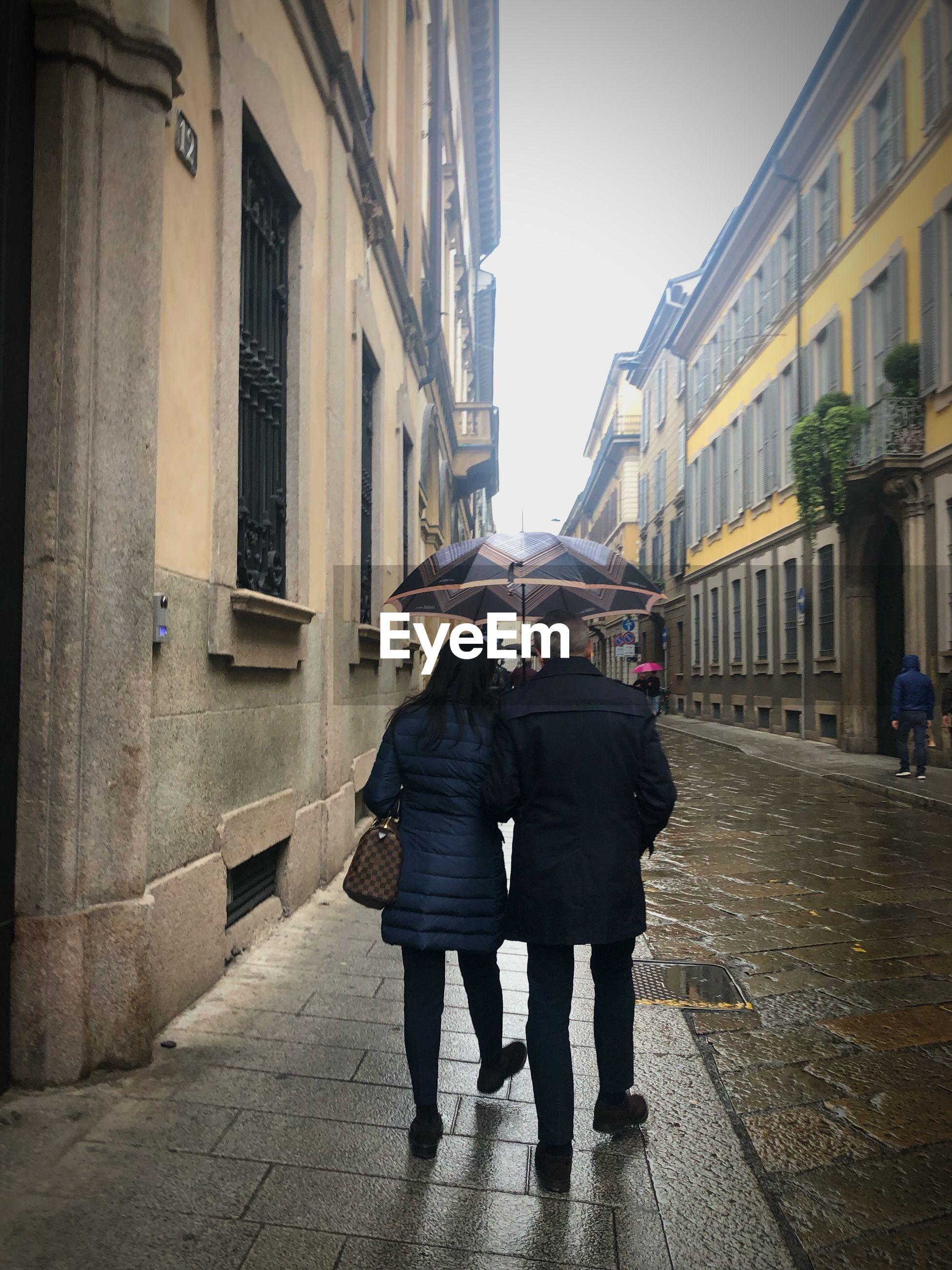 REAR VIEW OF FRIENDS WALKING ON STREET AMIDST BUILDINGS
