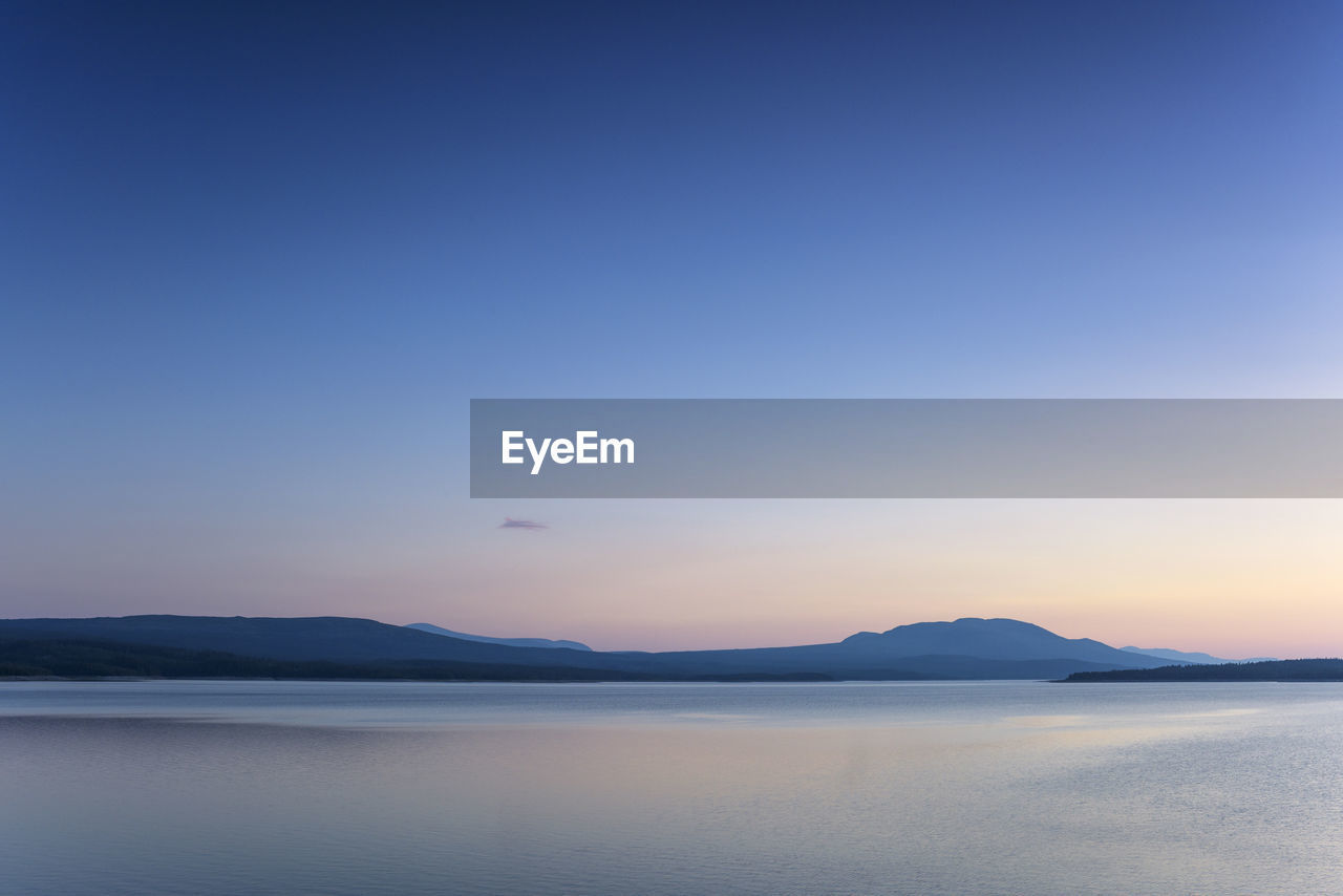 sky, scenics - nature, beauty in nature, water, tranquil scene, tranquility, copy space, mountain, blue, sea, sunset, waterfront, idyllic, nature, clear sky, no people, non-urban scene, flying, bird, outdoors, salt flat