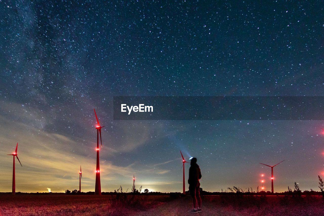 Rear view of man looking at illuminated windmills against star field