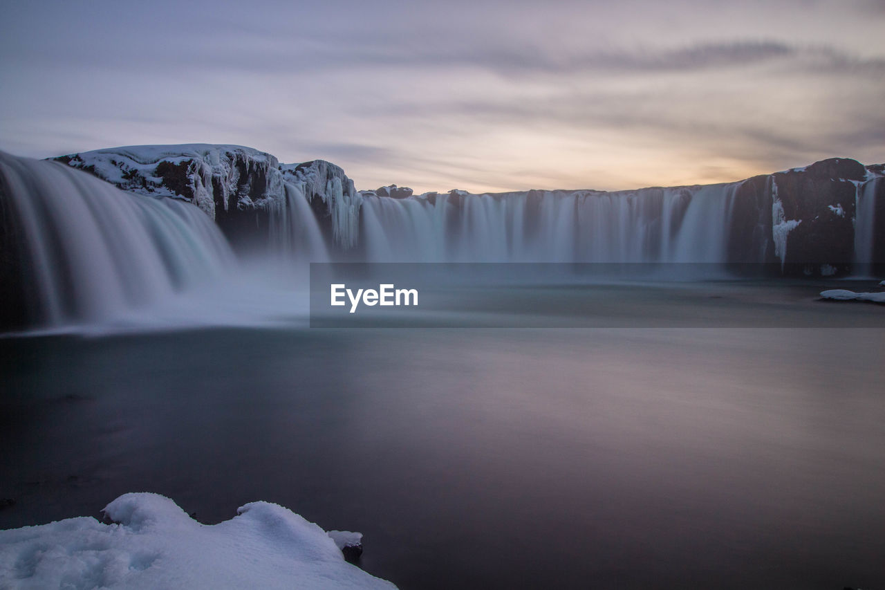 SCENIC VIEW OF WATERFALL AGAINST SKY IN WINTER