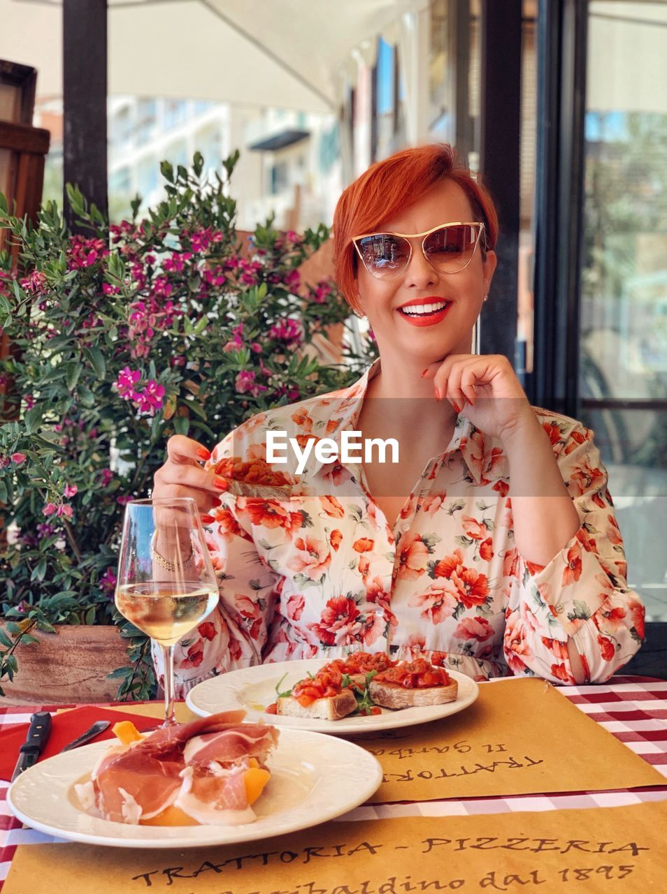 smiling, one person, glasses, young adult, table, portrait, sunglasses, food and drink, sitting, looking at camera, front view, lifestyles, fashion, young women, drink, restaurant, adult, happiness, leisure activity, glass, hairstyle, beautiful woman, outdoors