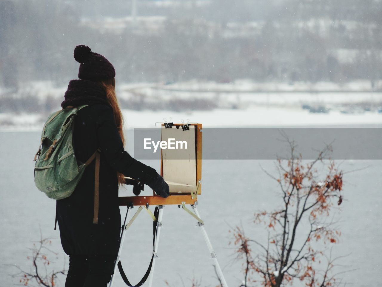 Side view of woman holding suitcase against lake during snowfall