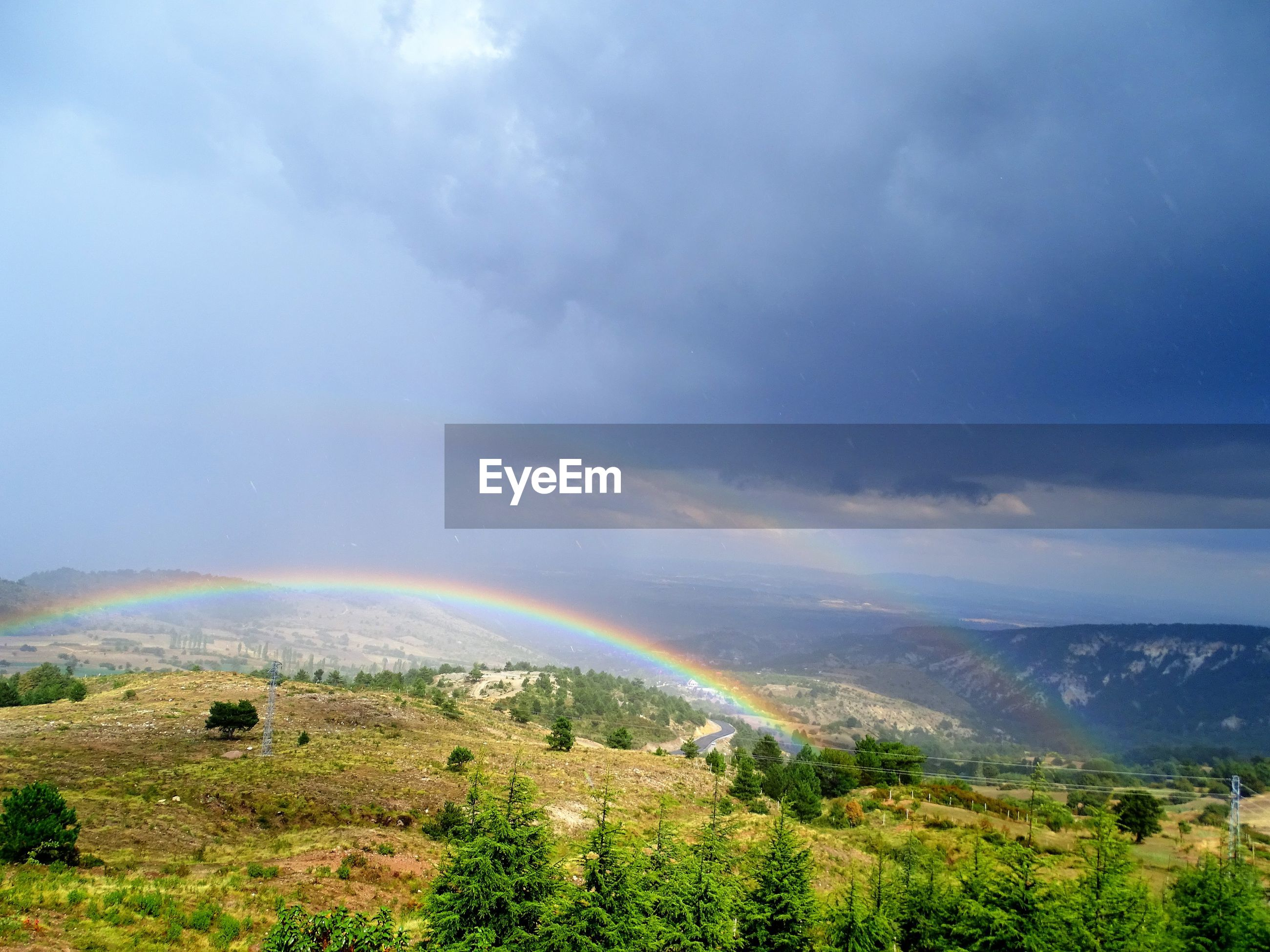 Scenic view of double rainbow on landscape against cloudy sky