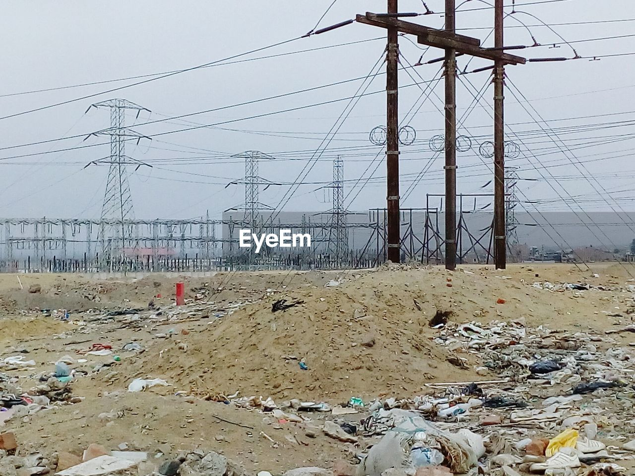 electricity, electricity pylon, cable, power line, technology, sky, connection, fuel and power generation, power supply, land, day, no people, nature, outdoors, environment, transportation, built structure, garbage, complexity, messy, electrical equipment, pollution, chaos