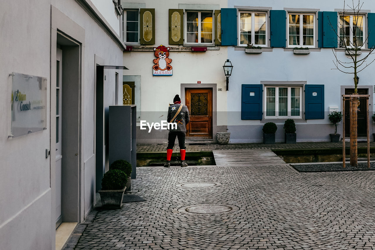 architecture, building exterior, real people, built structure, cobblestone, one person, full length, men, walking, rear view, outdoors, day, residential building, cleaning, people