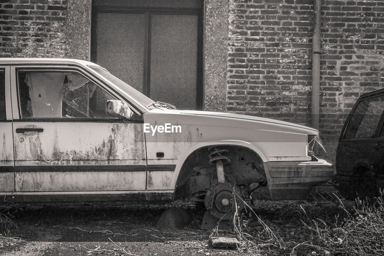 abandoned, mode of transportation, transportation, architecture, day, land vehicle, building exterior, built structure, no people, old, damaged, obsolete, run-down, deterioration, field, decline, brick wall, land, brick, outdoors, wheel, ruined, garage