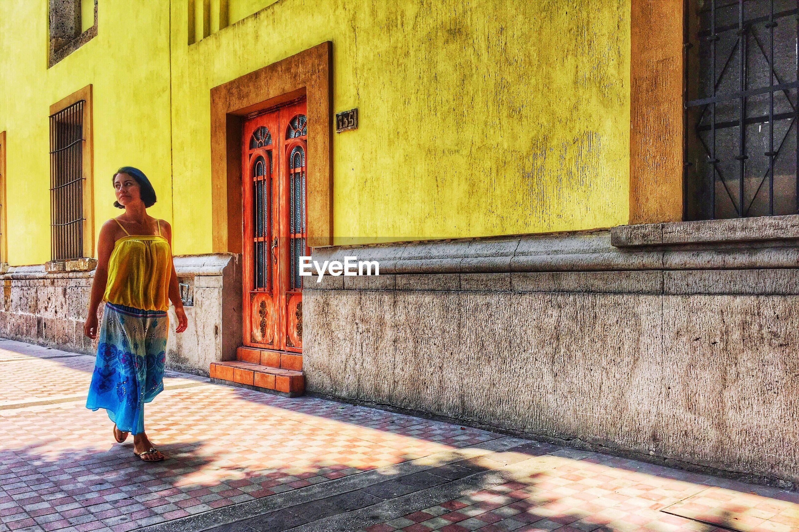 FULL LENGTH REAR VIEW OF A WOMAN WALKING ON STREET