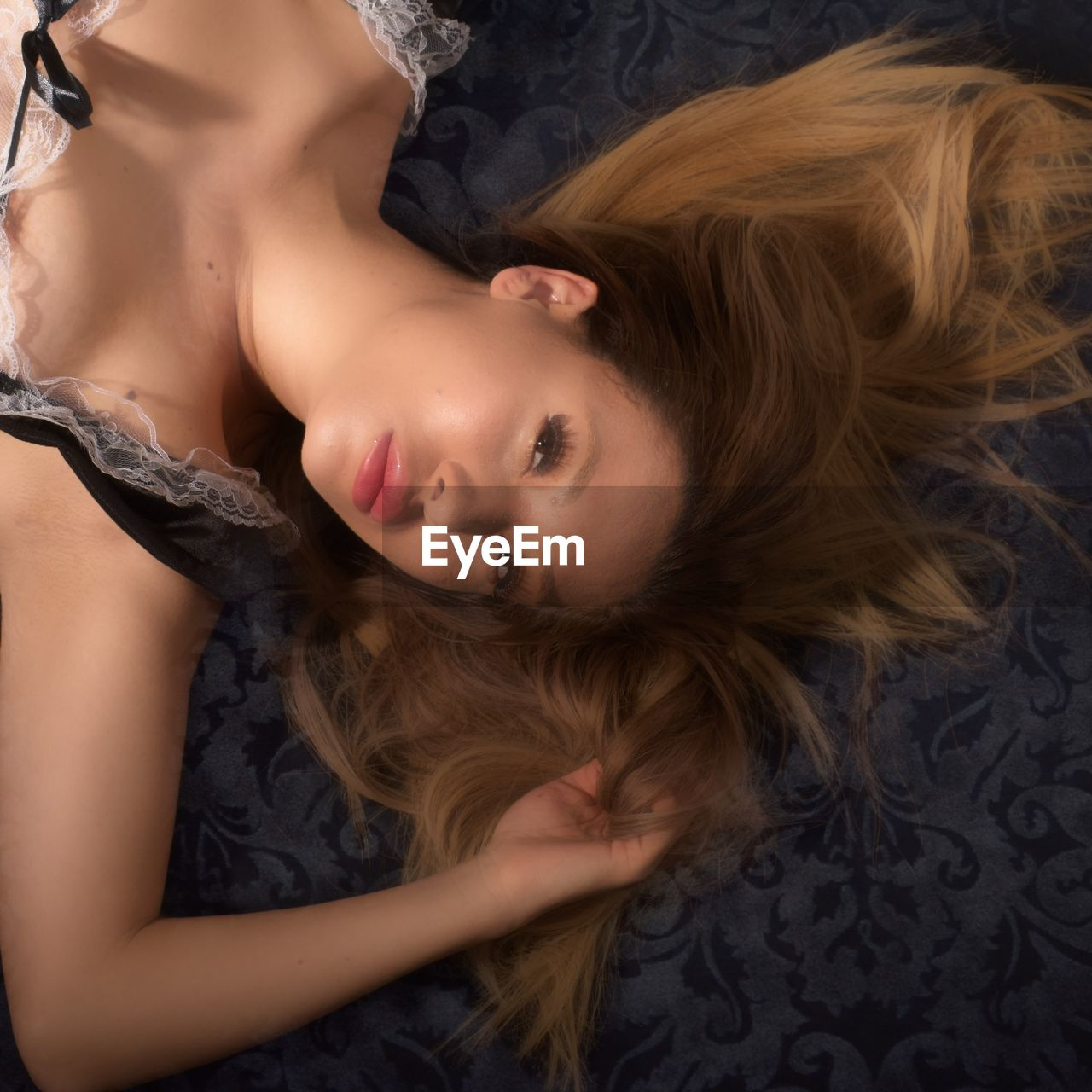 lying down, young adult, hair, lifestyles, real people, hairstyle, indoors, young women, portrait, bed, women, beautiful woman, headshot, adult, leisure activity, long hair, beauty, people, high angle view