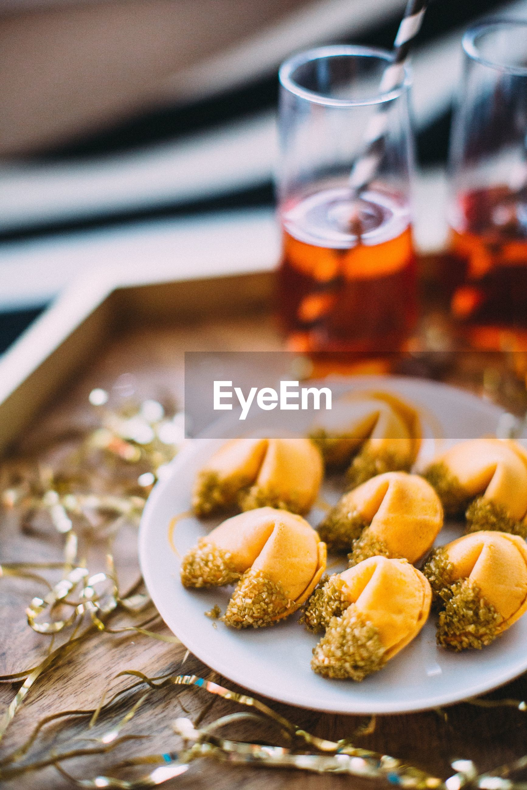 Close-up of fortune cookies and drink in tray on table