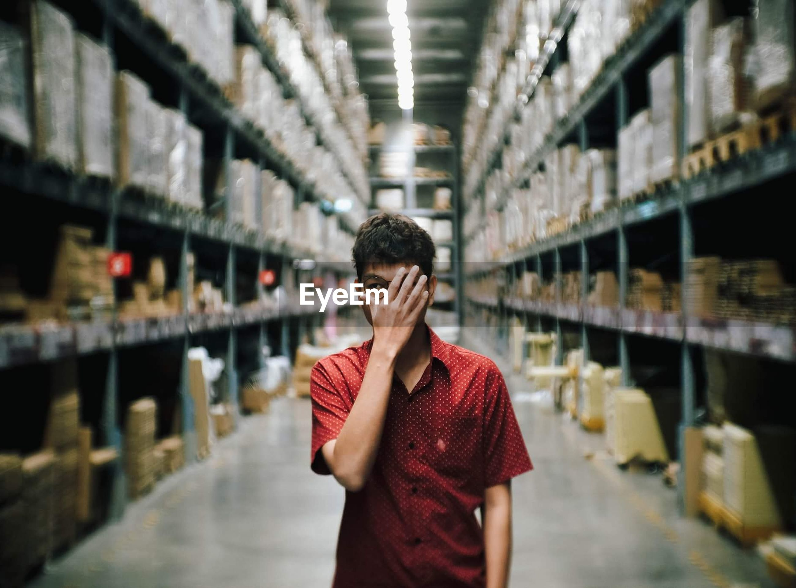 Man covering face with hand while standing amidst shelves at factory