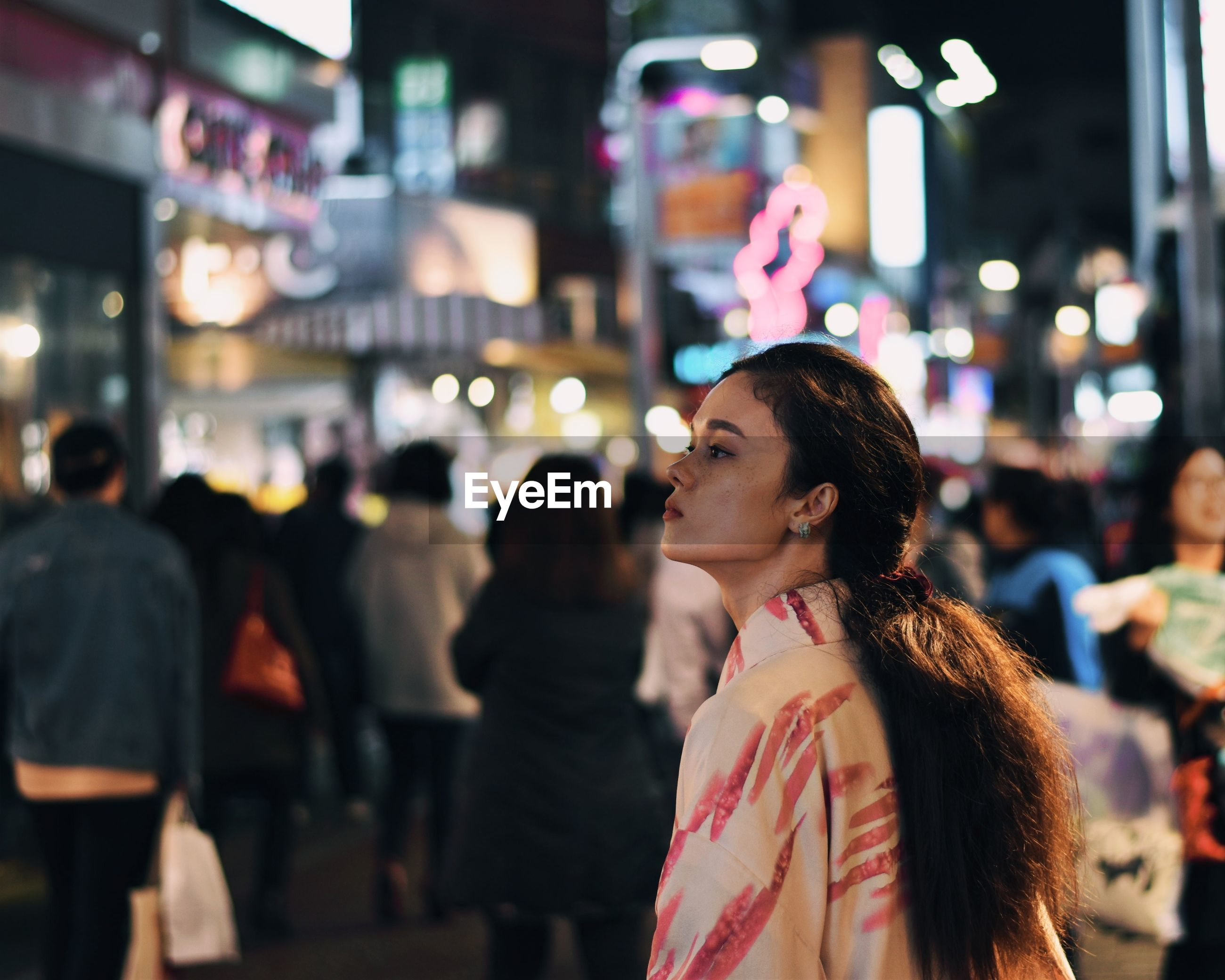 Woman looking away while standing in illuminated city at night