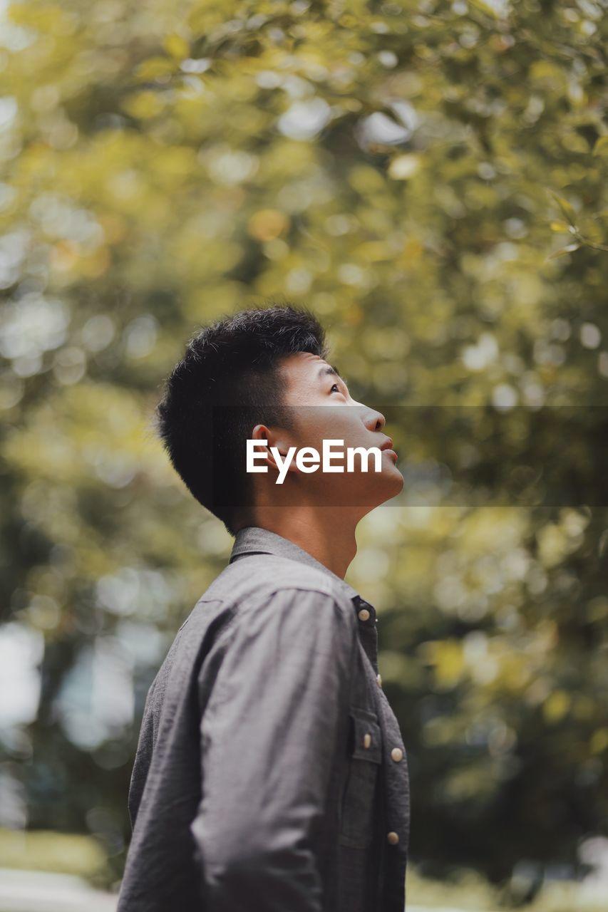 Man Looking Away Against Trees